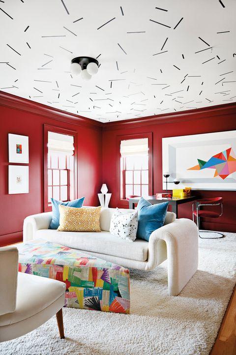 Angela Chrusciaki Blehm diseña este salón rojo lleno de color con el techo con papel pintado