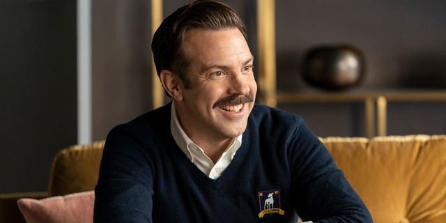 man with mustache and dark blue sweater