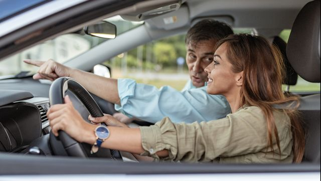 teen driver learning parallel parking with driving instructor