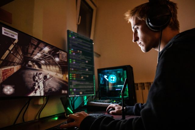 teenage boy playing multiplayer games on desktop pc in his dark room   stock photo