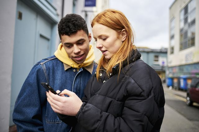 teenage couple looking at smartphone and smiling, looking for directions or social media while in the street