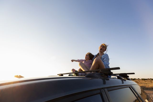 teenage girl and her younger brother on top of suv on desert road,
