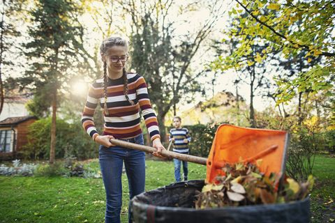 teenage girl composting autumn leaves