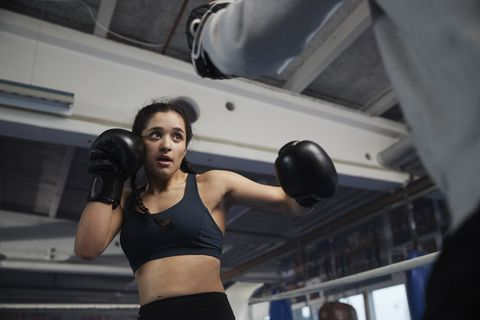 Teenage girl exercising with coach in boxing ring
