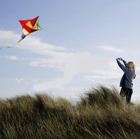 teenage girl flying a kite on the beach