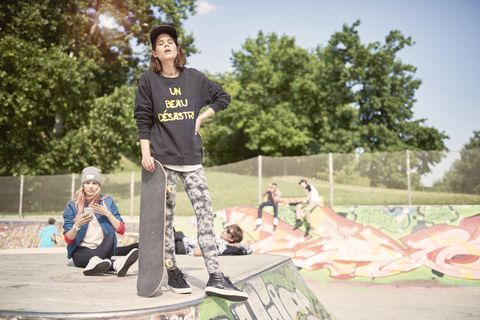 Teenage girl holding skateboard in skatepark