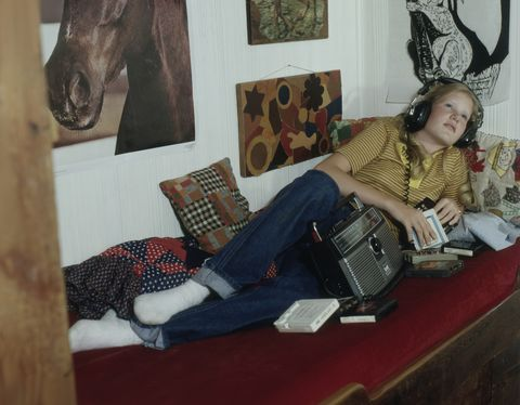 Teenage girl lying on bed listening to music