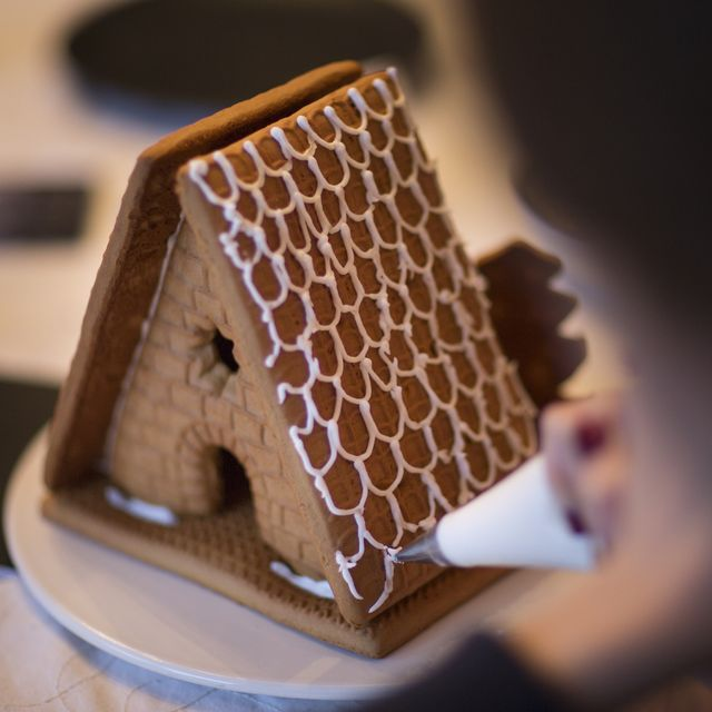 piping icing onto a gingerbread house