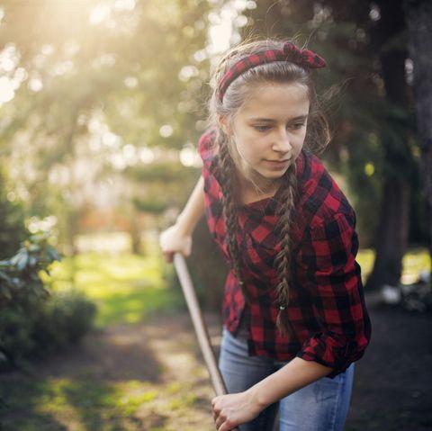teenage girl raking on sunny spring day