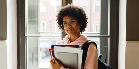 Teenage Girl Wearing Eyeglasses Holding Books At Home