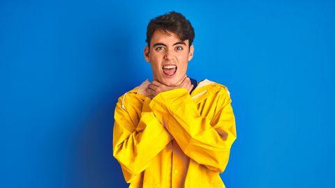 tiener met regenjas aan knijpt zijn eigen keel dicht