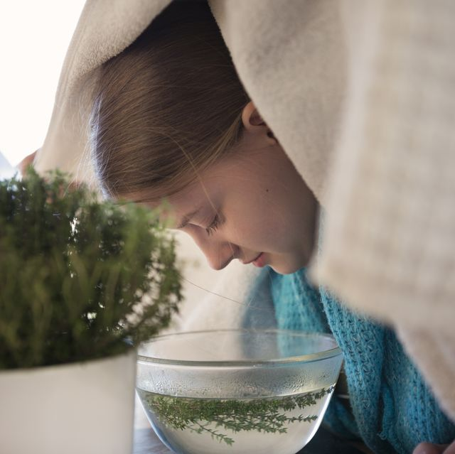 teenager using herbal steam inhalation as a remedy to treat respiratory symptoms of cold and flu virus