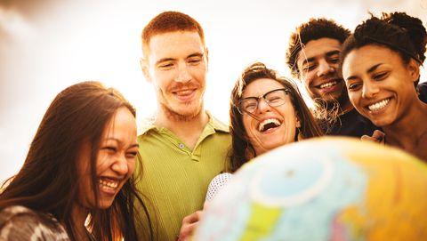 groep mensen staat om globe heen en lacht