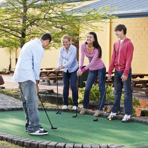 teenagers playing mini golf