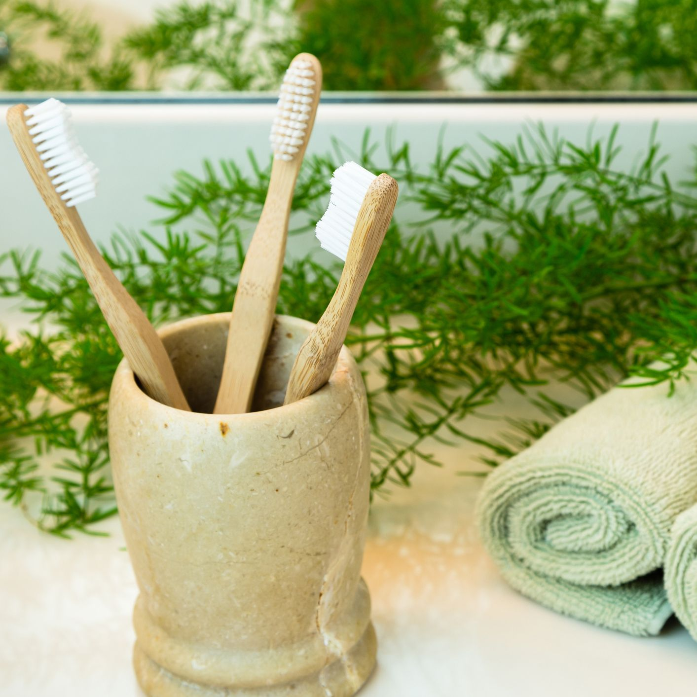Bamboo toothbrushes in cup, towels and greens on bathroom countertop