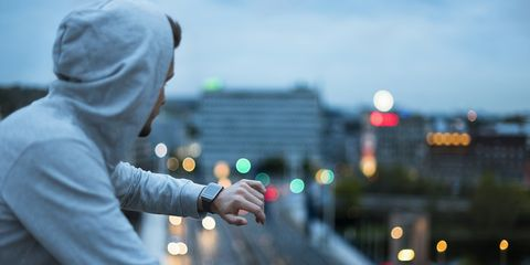 Athlete checking his smartwatch above the city at dawn