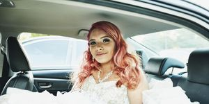 Smiling young woman in quinceanera gown sitting in back seat of car