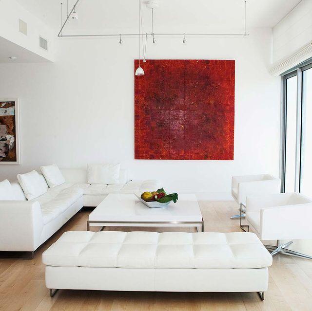 salón decorado en blanco con una pintura roja