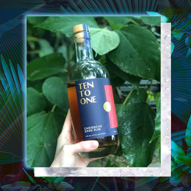 danielle holding bottle of ten to one rum with leaves in background