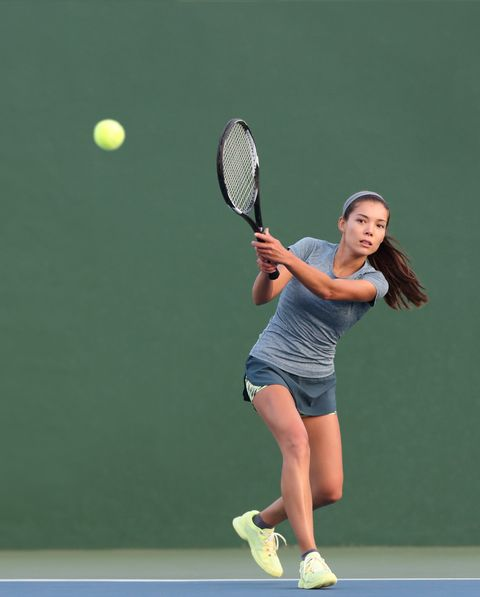 tennis playing woman hitting ball on green hard courtasian athlete girl returning serve with racket wearing skort and shoes