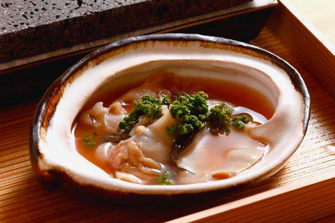 「日本料理 寺田」酒盗のソースに漬けた鮑とはまぐりに、花山椒を散らした焼き物。熱した溶岩プレートにのせた瞬間、広がる香ばしさに食欲をそそられる。