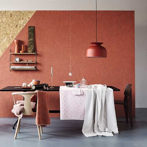 """Pops of terracotta can work well to add warmth, here a wall painted in """"Red Earth"""" by Farrow & Ball is beautifully balanced by grey, pale pink and natural woods. The pendant light is by Oliver Schick for Gubi, from £186; the sculptural pots on the shelf are by Benjamin Hubert, from £45 each. And the pale pink throw on the white oak chair (from &Tradition, £329, Nest) is from Society Limonata, and the rust coloured throw is from Missoni Home, £244 from Amara. Styling: Tina Hellberg; Photographer: Magnus Anesund."""