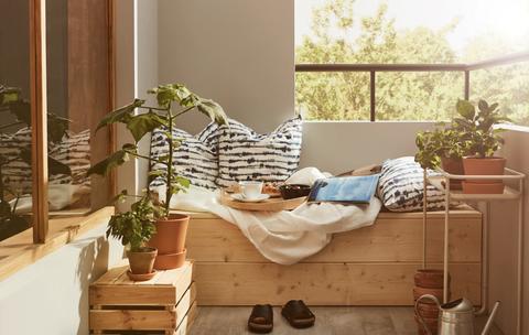 Terraza decorada con plantas y un banco de madera