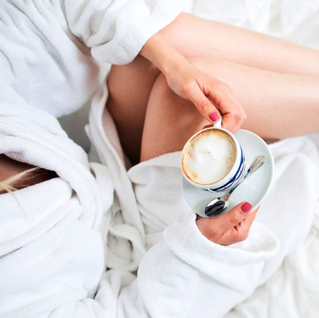 woman in terrycloth robe with breakfast in bed