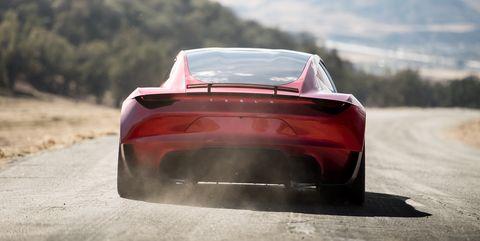 tesla roadster 2022 acelera a fondo en una carretera desierta en vista trasera