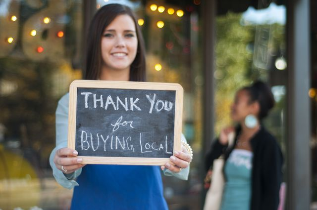 woman holding a sign that says thank you for buying local