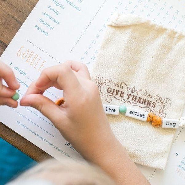 child making thanksgiving charm bracelet