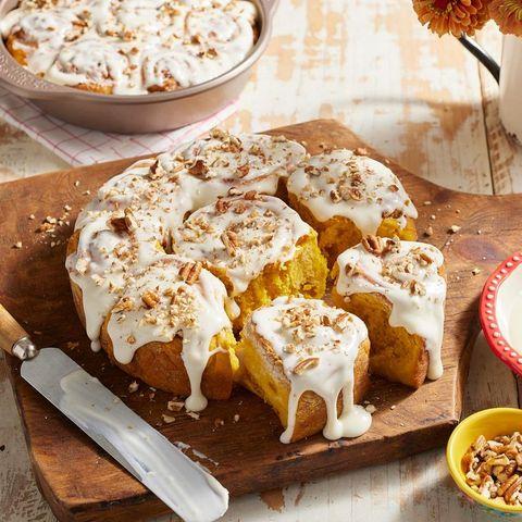 pumpkin spice cinnamon rolls on wood board