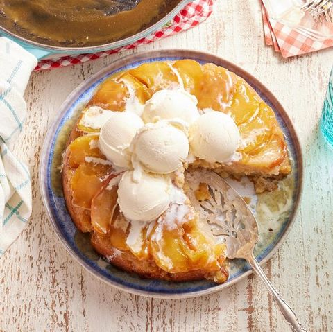 apple cake in an iron skillet with ice cream on top