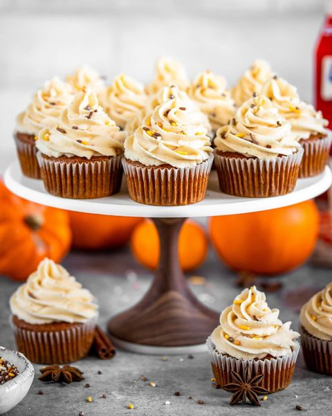 pumpkin spice cupcakes on cake stand with pumpkins behind