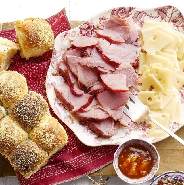 honey glazed ham with checkerboard rolls on platter with cheese slices
