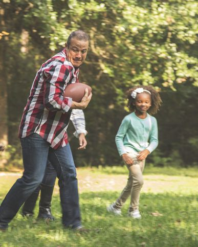 multi ethnic, multi generation family members playing a football game together in grandparents backyard on thanksgiving day  family in sports