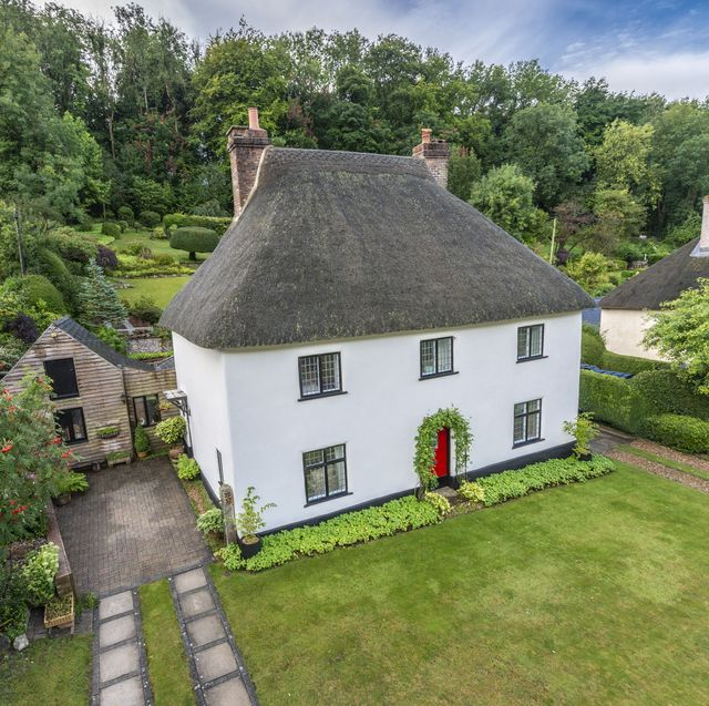 thatched cottage with a white exterior is up for sale in a quaint dorset village