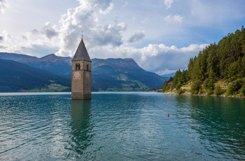 the bell tower of the sunken church in curon, resia lake, bolzano province, south tyrol, italy