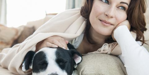 Woman relaxing on sofa with dog