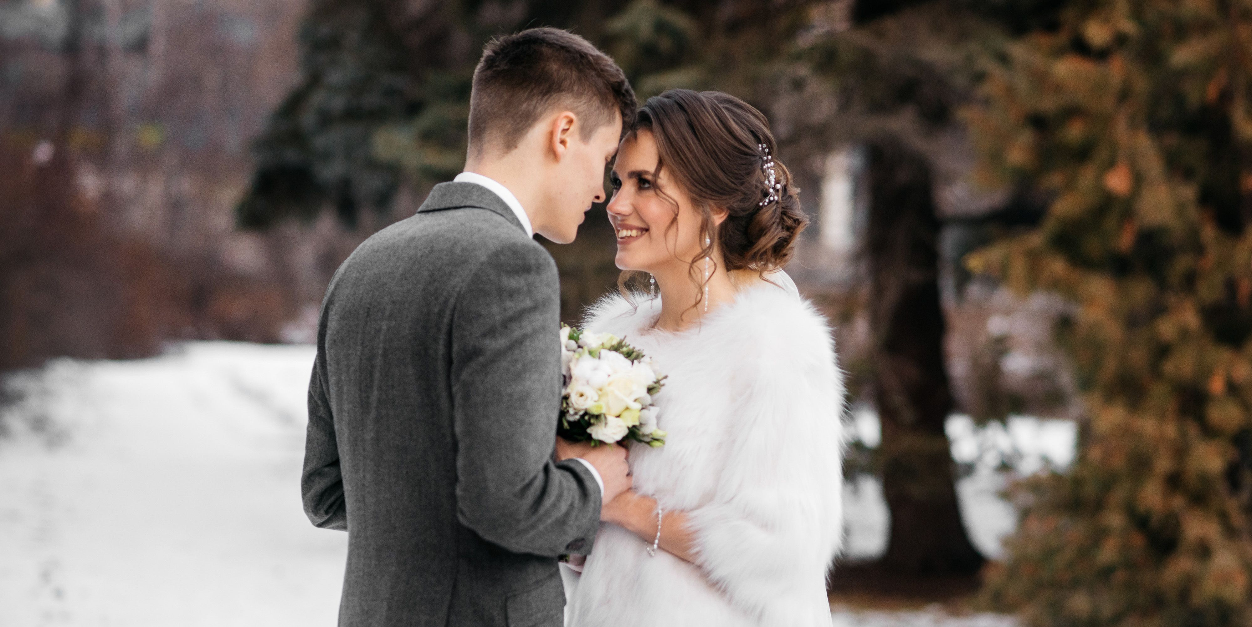 The bride and groom stand in the winter park, huddled together