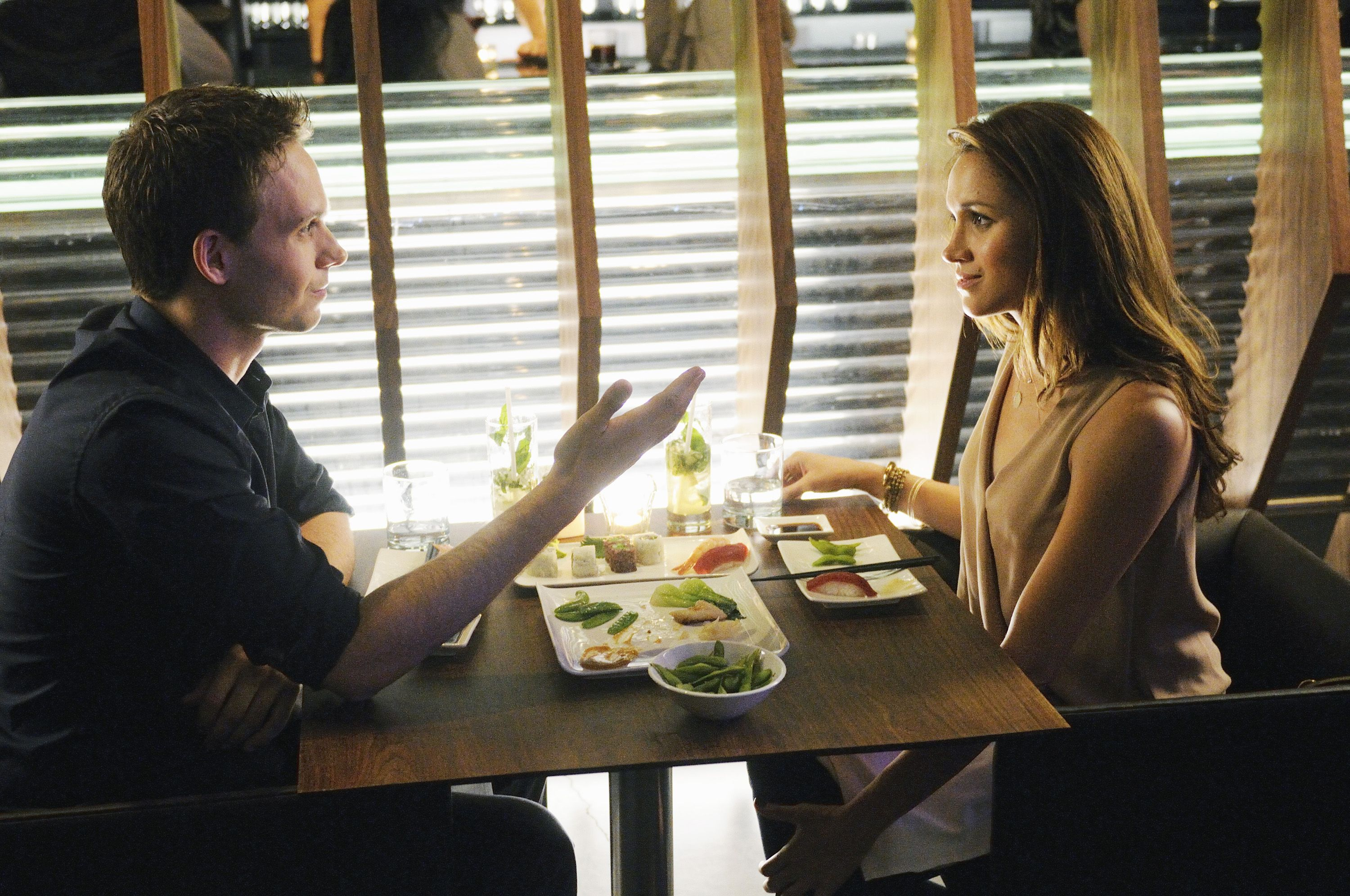 Patrick J. Adams as Mike Ross and Meghan Markle as Rachel Zane sit down for some sushi on Suits.