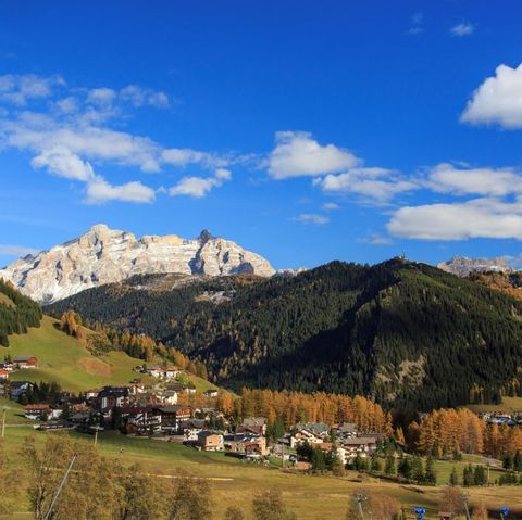 The colorful woods frame the village and the high peaks in autumn Gardena Valley. Trentino-Alto Adige. Italy. Europe