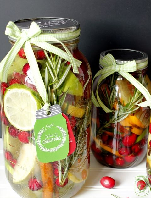 two mason jars filled with clear liquid and cranberries, oranges, limes and cinnamon sticks with ribbon around the lids one has a tag in the shape of a mason jar reading merry christmas