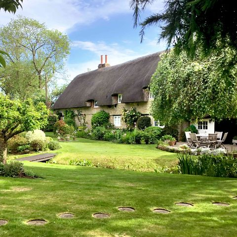 beautiful cottage for sale with a thatched roof