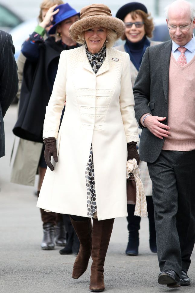 The Duchess of Cornwall attended 'Ladies Day' at the Cheltenham Races wearing a structured white coat with intricate embellishments over a polka dot dress. She topped off the look with chocolate brown boots, gloves, and bag, a tan fur-trimmed hat, and pearl drop earrings.