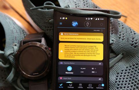 un reloj garmin y un móvil con la imagen de la aplicación de garmin informando del ciberataque sufrido para secuestrar sus datos
