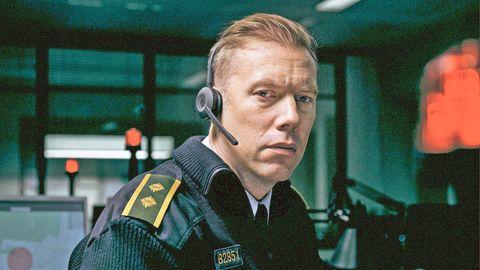 jakob cedergren lleva uniforme de oficial de policía y un micrófono de diadema de centralita telefónica en una imagen promocional de the guilty