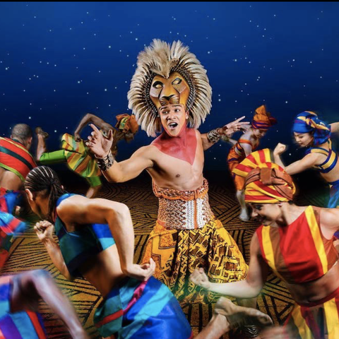 actor dressed as lion surrounded by dancers in 'the lion king' on broadway