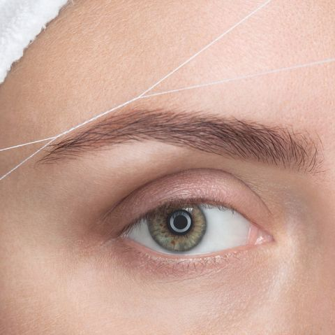 The make-up artist plucks her eyebrows with a thread close-up.
