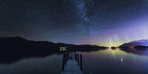 The Milky Way and Aurora Borealis from a jetty over Derwent water. English Lake District. UK